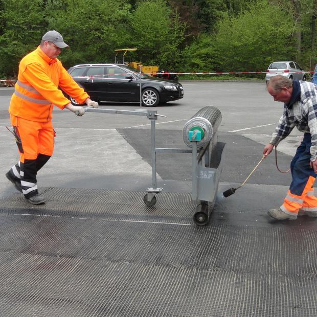 Manual application of S&P asphalt reinforcement (local surfaces)
